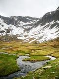与水小河的下雪的山  免版税库存照片