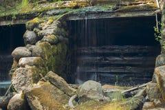 与水小河的老,被放弃的水车和小的瀑布 免版税库存图片