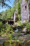 与水小河的老,被放弃的水车和小的瀑布 库存图片