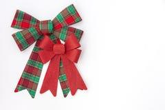 与更小的红色假日弓的大红色和绿色格子花呢披肩弓 免版税库存照片