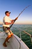 与从小船的钓鱼者渔夫大鱼战斗 库存照片