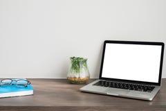 与黑屏的办公室桌在glas的膝上型计算机和庭院树 库存照片