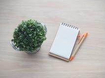 与黑屏的木办公室桌在文本的a笔记本纸 免版税库存图片