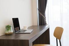 与黑屏膝上型计算机,加奶咖啡杯子的办公室桌,现代 免版税库存图片
