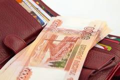 与货币和银行信用卡的持有人 免版税库存图片