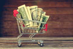 与货币的购物车 免版税库存照片