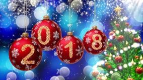 与2018年垂悬在一蓝色bokeh和一棵转动的圣诞树的背景的第的红色球 免版税库存图片