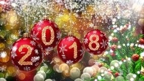 与2018年垂悬在bokeh和一棵转动的圣诞树的背景的第的红色球 免版税库存图片