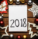 与2018年手写文本的圣诞节和新年卡片,嘲笑或者删去在葡萄酒木桌上的笔记本 库存照片