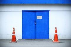 与仓库特写镜头和路锥体的蓝色门 免版税库存图片