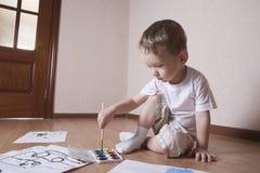 与水彩和油漆刷的男孩绘画 库存图片