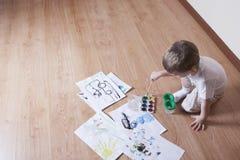 与水彩和油漆刷的男孩绘画 免版税库存照片