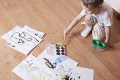 与水彩和油漆刷的男孩绘画 免版税库存图片