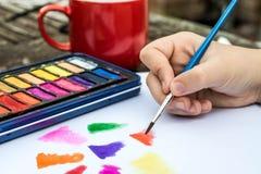 与水彩油漆的儿童绘画在一本白皮书书 图库摄影