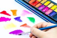与水彩油漆的儿童绘画在一本白皮书书 库存照片
