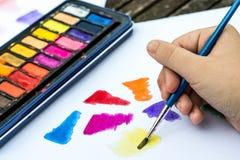 与水彩油漆的儿童绘画在一本白皮书书 免版税库存照片