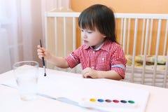 与水彩油漆的可爱的小男孩绘画 免版税库存照片