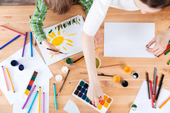 与水彩油漆的小的儿子和母亲绘画在桌上 免版税库存图片