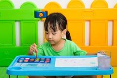 与水彩的亚洲矮小的中国女孩绘画 库存图片