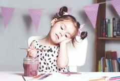 与水彩的俏丽和逗人喜爱的小女孩绘画图片在演播室 教育过程的概念 免版税库存图片