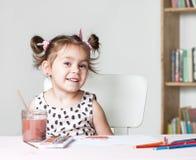 与水彩的俏丽和逗人喜爱的小女孩绘画图片在演播室 教育过程的概念 库存图片