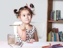 与水彩的俏丽和逗人喜爱的小女孩绘画图片在演播室 教育过程的概念 库存照片