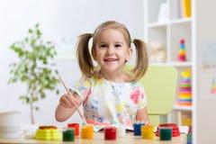 与水彩的俏丽的孩子女孩绘画在家 免版税库存照片