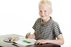 与水彩的创造性的年轻男孩绘画 库存图片