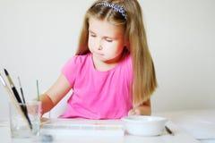 与水彩的可爱的女孩绘画在一个晴朗的绝尘室在 库存照片