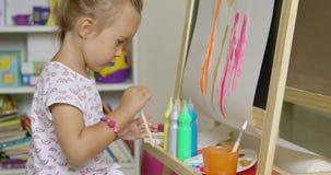 与水彩的逗人喜爱的矮小的白肤金发的女孩绘画 影视素材