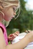 与水彩(水彩)的儿童白肤金发的女孩绘画,绘画一个纸碟 图库摄影