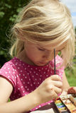 与水彩(水彩)的儿童白肤金发的女孩绘画,绘画一个纸碟 库存照片