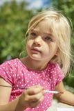 与水彩(水彩)的儿童白肤金发的女孩绘画,绘画一个纸碟 库存图片
