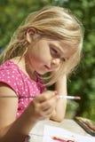 与水彩(水彩)的儿童白肤金发的女孩绘画,绘画一个纸碟 免版税图库摄影