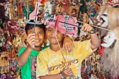 与阴影木偶的兴高采烈的巴厘语儿童游戏 免版税库存图片