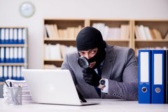 与巴拉克拉法帽的犯罪商人在办公室 免版税库存照片