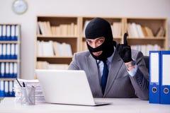 与巴拉克拉法帽的犯罪商人在办公室 图库摄影
