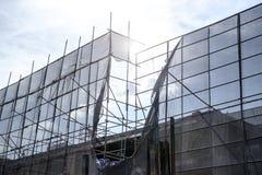 与围拢大厦的脚手架和蓝色防护网的建筑背景在整修下 免版税库存照片