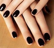 与黑指甲油的被修剪的钉子 与黑暗nailpolish的修指甲 时尚与发光的胶凝体亮漆的艺术修指甲 免版税图库摄影