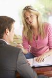 与财政顾问的妇女会谈在家 免版税图库摄影