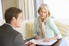 与财政顾问的资深妇女会谈在家 库存照片