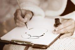 画与贷方的女性的手一幅讽刺画 库存照片