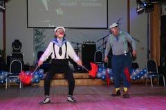 与令旗的水手可笑的流行音乐数字由笑剧手势剧院和扮小丑的演员执行了, Litsedei 免版税库存图片