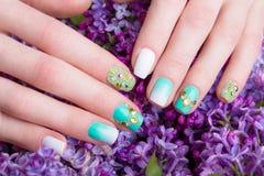 与水晶的美好的绿松石修指甲在女性手上 特写镜头 库存图片