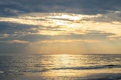 与黑暗的云彩的黄色温暖的太阳光在海 库存照片