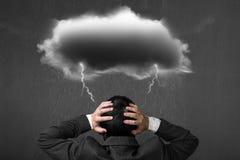 与黑暗的云彩雨闪电的沮丧的商人在他的他 库存图片