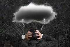 与黑暗的云彩雨闪电的沮丧的商人在他的他 免版税库存照片