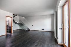 与黑暗的木条地板和楼梯的现代空的内部 免版税图库摄影