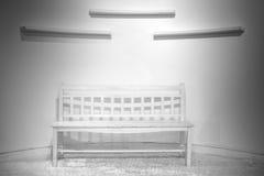 与黑暗的白色墙壁的空的椅子 库存照片