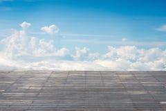 与晴朗的天空cloudscape的老垂直的镶边木大阳台 免版税库存照片